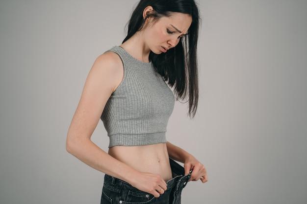 Девушка сильно похудела. анерексия у девочки. слишком большие джинсы для худощавой девушки.