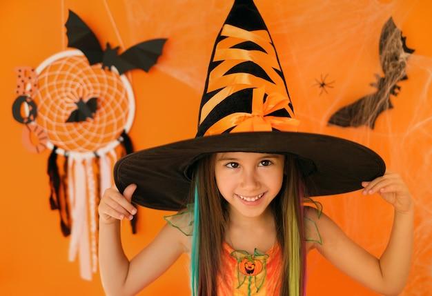 Девушка корчит гримасу и смеется на оранжевом фоне с декором на хеллоуин.