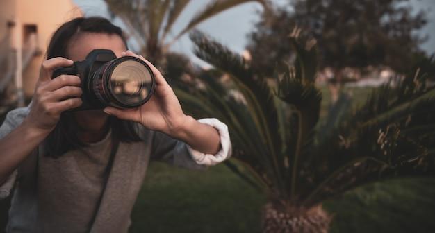 소녀는 자연에서 야외에서 전문 slr 카메라로 사진을 닫습니다.