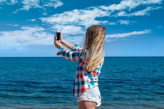그 소녀는 바다를 배경으로 전화로 셀카를 만든다.