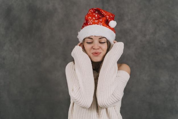 소녀는 새해를 기원합니다. 빨간 산타 클로스 모자에있는 여자. 산타 모자에 꿈꾸는 소녀.
