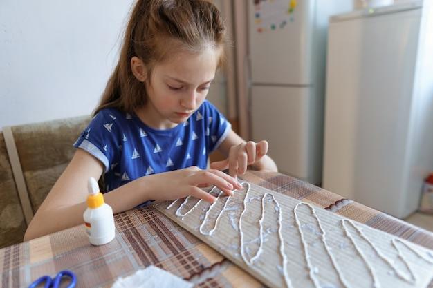 女の子は工芸品を作り、段ボールを接着し、家庭の台所に座っています