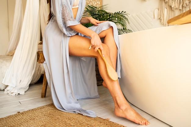 女の子はお風呂でブラシを使ってマッサージをします。彼女は美しい日焼けした足を持っています。彼女はリンパの抗セルライトマッサージをします