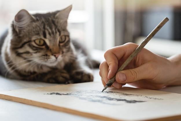 소녀는 오래된 만년필로 스케치를하고 고양이는 근처에 앉아 있습니다.