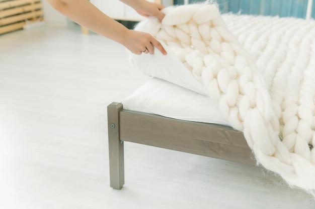 Девушка застилает постель одеялом