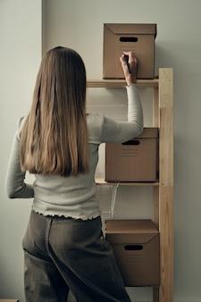 女の子は木製の棚に紙箱を作ります。環境に優しい保管と包装。