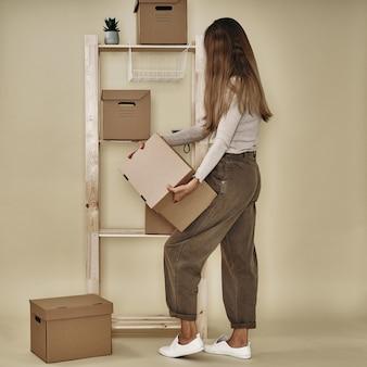 Девушка составляет бумажные коробки на деревянной стойке. экологичное хранение и упаковка.