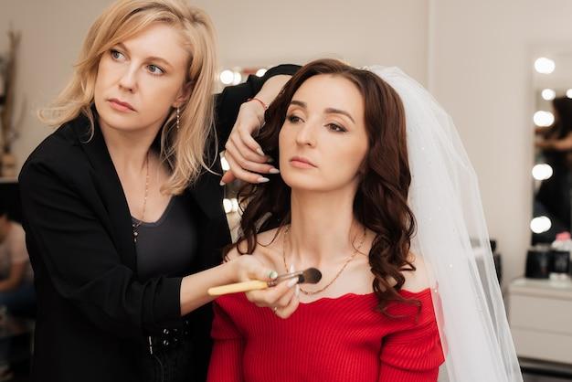 Визажист-девушка кисточкой наносит хайлайтер на светлые участки кожи модели, чтобы придать блеск.