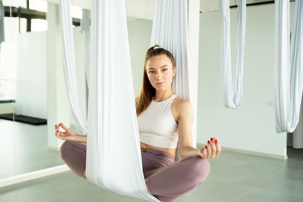 女の子は白いハンモックで瞑想します。彼女はフライヨガを練習しています。心身の健康の概念