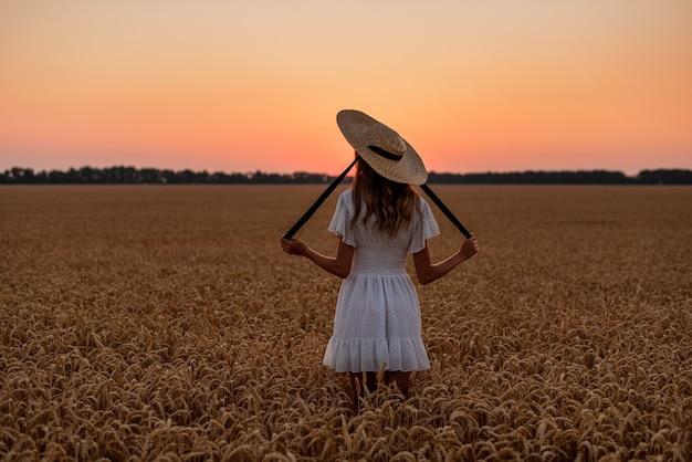 소녀는 머리에 밀밭에서 새벽을 만난다 리본이 달린 밀짚모자
