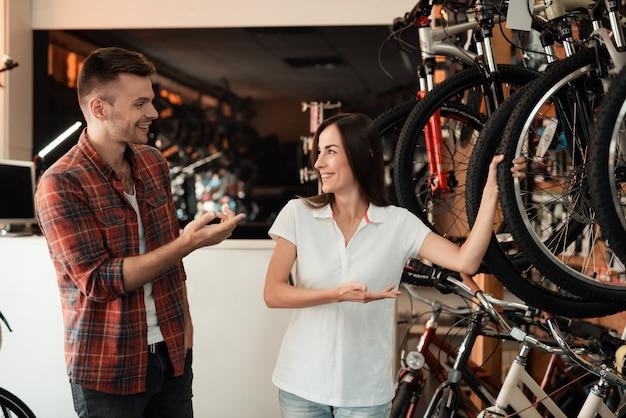 Девушка предлагает покупателю купить велосипед.