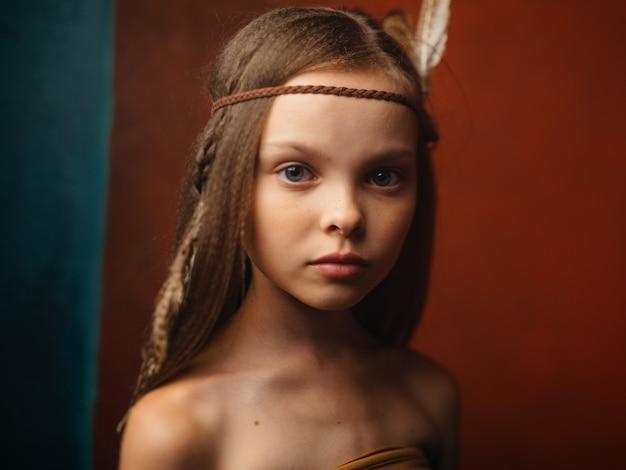 野蛮な羽の頭に飾りを付けた赤い背景の女の子