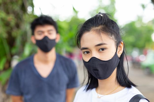 Девушка на улице надевает маску для лица, чтобы предотвратить вирус и противостоять дымке.