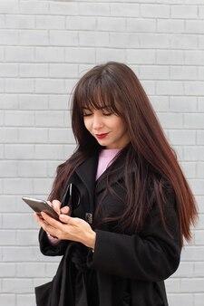 Девушка на улице пишет сообщение на скане
