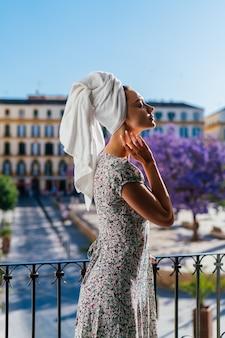 기쁨과 함께 호텔에서 휴가를 보내는 소녀는 열린 발코니에서 공기를 흡입합니다.