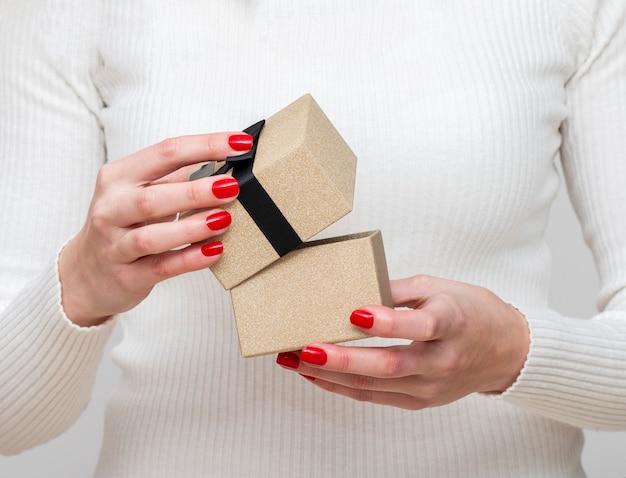 Девушка красиво раскрывается, чтобы упаковать подарок в стильную коробку с лентой.