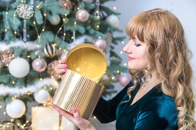 Девушка открывает рождественские подарки. выборочный фокус. праздничный день.