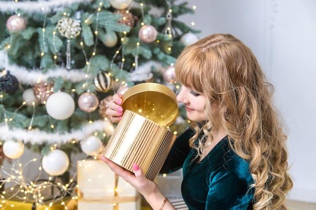 女の子はクリスマスプレゼントを開きます。セレクティブフォーカス。ホリデー。