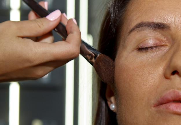 Девушка наносит пудру на лицо, завершает макияж дымчатых глаз в салоне красоты. профессиональный уход за кожей.