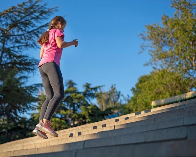 소녀는 신체 운동을하고 계단을 뛰어 올라간다