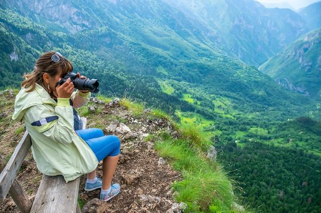 ベンチの女の子の写真家は、山の頂上から美しい景色の写真を撮ります。