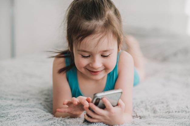 女の子は携帯電話でゲームをし、子供のガジェット中毒の女の子がメッセージを書く