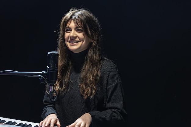 소녀는 녹음 스튜디오 전문 녹음에서 피아노를 연주한다