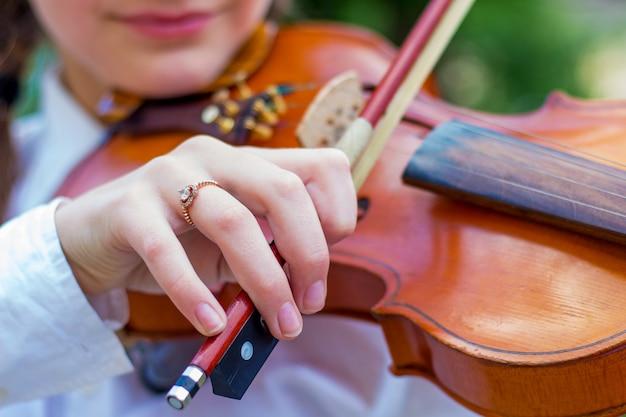 소녀는 바이올린을 연주하고 소녀의 손은 바이올린 활