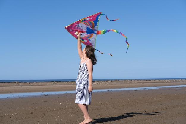 女の子は海で凧で遊ぶ