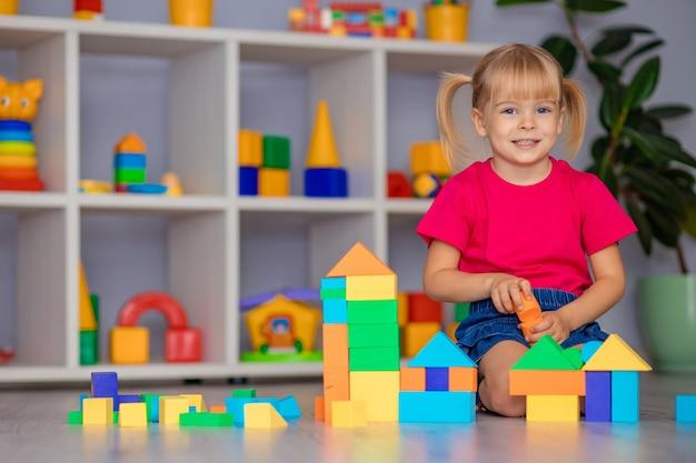 Девочка играет в игрушки дома, в детском саду или в яслях. развитие ребенка.