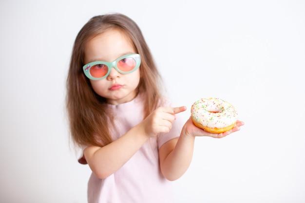 Девушка с недовольным лицом показывает пальцем на пончик эмоции вредная еда правильное питание детское питание