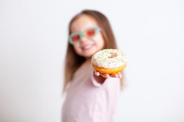 Девушка с недовольным лицом показывает пальцем на пончик эмоции вредная еда