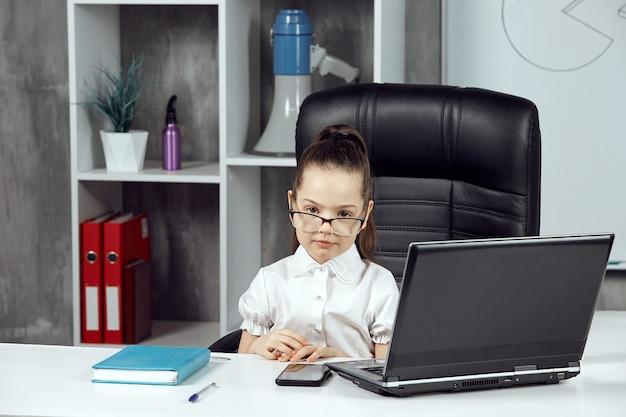 소녀는 카메라 앞에서 포즈를 취하는 흰색 테이블에서 에이전시 대표를 묘사합니다.