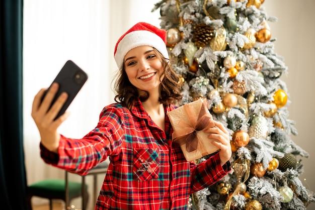 소녀는 크리스마스 트리 근처에서 포즈를 취하고 셀카를 찍습니다. 한 여성이 온라인으로 전화로 친척에게 축하를 보냅니다. 그녀는 그녀의 손에 선물을 들고 웃 고.