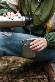 Девушка наливает в лесу ароматный чай из термоса. пикник в сосновом лесу