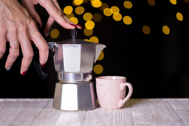Девушка наливает кофе из гейзерной кофеварки в чашку и боке на заднем плане