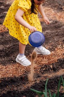 소녀는 정원에 있는 야채와 함께 침대에 비료와 모래를 붓습니다. 소녀는 재배를 돕습니다...