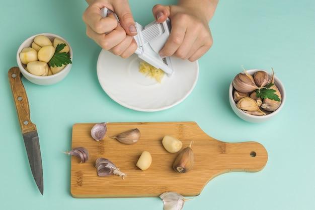 女の子はまな板の上におろし金でニンニクを処理します。キッチンに人気のスパイス。