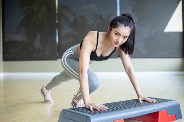 Девушка подталкивает ступеньками платформу в спортзале.