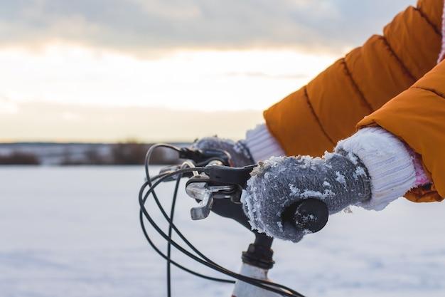 少女は冬の川を背景に自転車のホイールに手を置いた