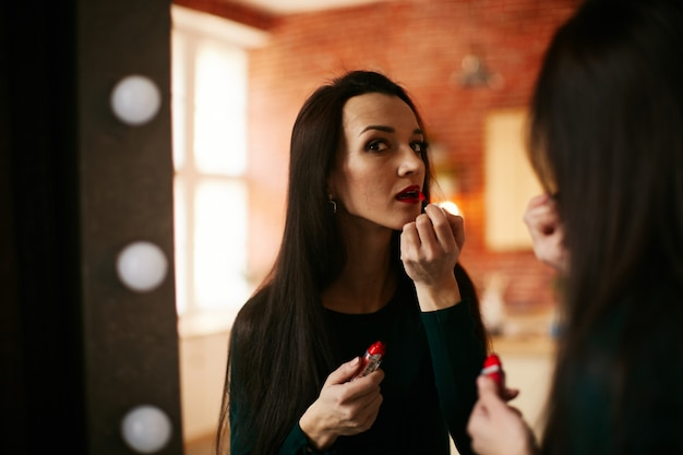 少女は彼女の唇に赤い口紅を置きます