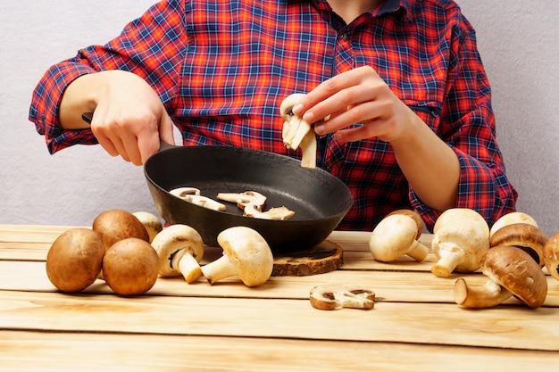 女の子は刻んだキノコを鍋に入れます。ファッショナブルな赤い格子縞のシャツの女の子は、木製のテーブルで食事を準備します