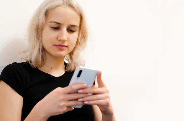 소녀는 전화로 나쁜 소식을 읽습니다. 소셜 네트워크. 세계 이벤트. 흰 바탕. 확대. 금발.