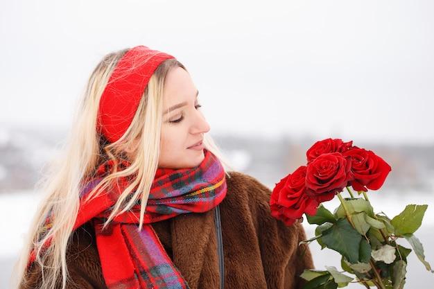 소녀는 발렌타인 데이에 빨간 장미 꽃다발을 선물로 받았습니다.
