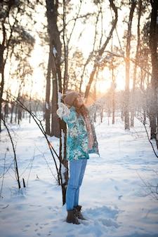 少女は日没の雪に覆われた森で冬に喜ぶ