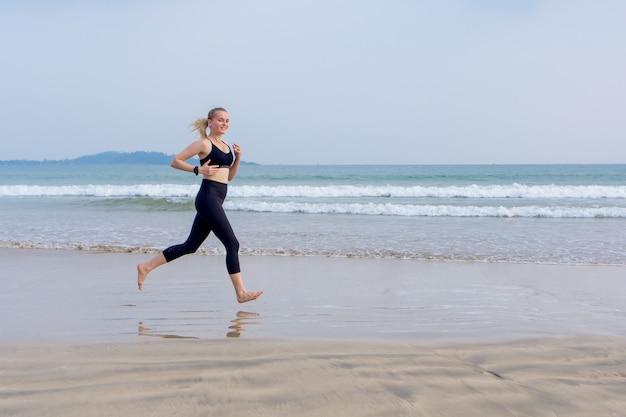 Девушка бегает по пляжу, занимается спортом