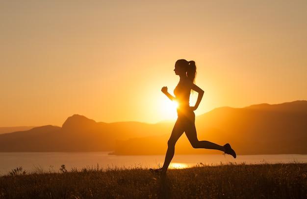 소녀는 바다의 산에서 뛰고 있습니다.