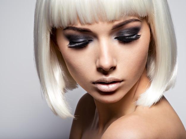 Лицо девушки крупным планом с длинными черными ресницами. модный макияж