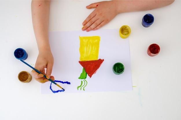소녀의 손은 도화지에 색색의 물감으로 집을 그립니다