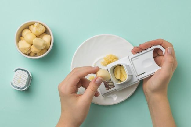 女の子の手はおろし金で新鮮なニンニクで扱われます。キッチンに人気のスパイス。